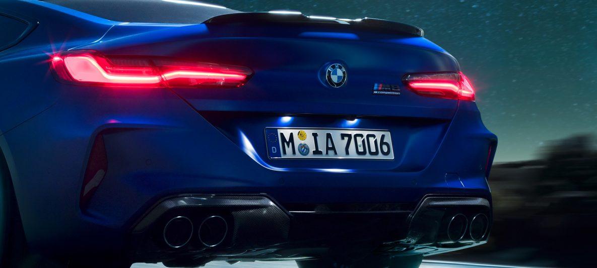 BMW M8 Competition Coupé in Marina Bay Blau metallic, Nahaufnahme Heck bei Nacht mit M Diffusor in Carbon Schwarz.