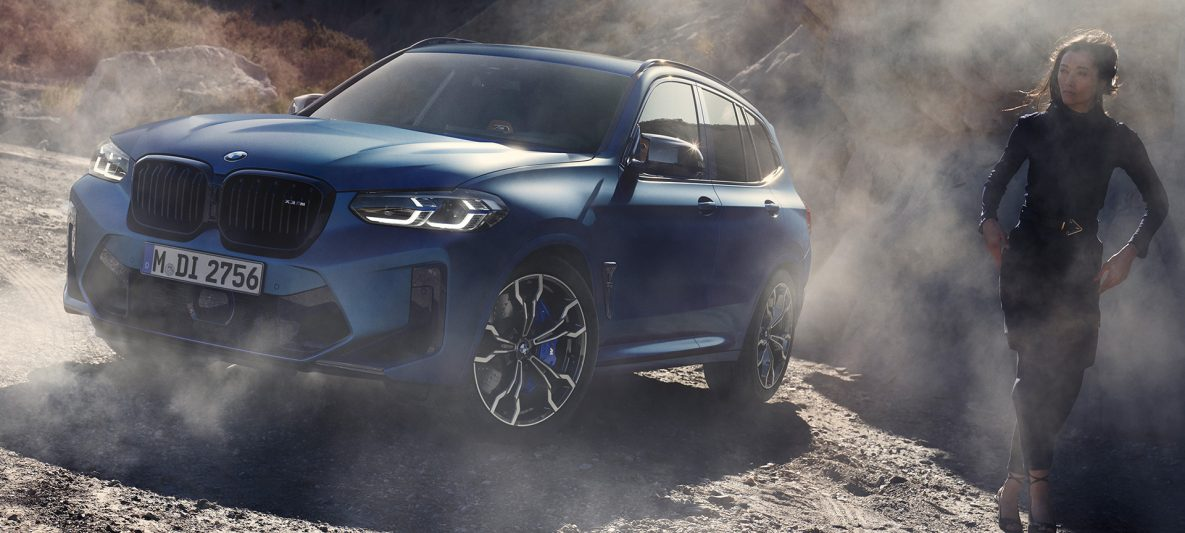 BMW X3 M Competition F97 LCI Facelift 2021 Frozen Marina Bay Blau metallic Dreiviertel-Frontansicht stehend in steinigem Gelände mit weiblichen Model